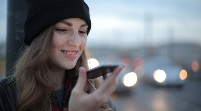 Happy-young-woman-searching-on-mobile-with-voice